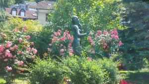 A statue of a woman with one hand to her ear and one hand gesturing slow down stands amidst blooming July flowers in Thun Switzerland.